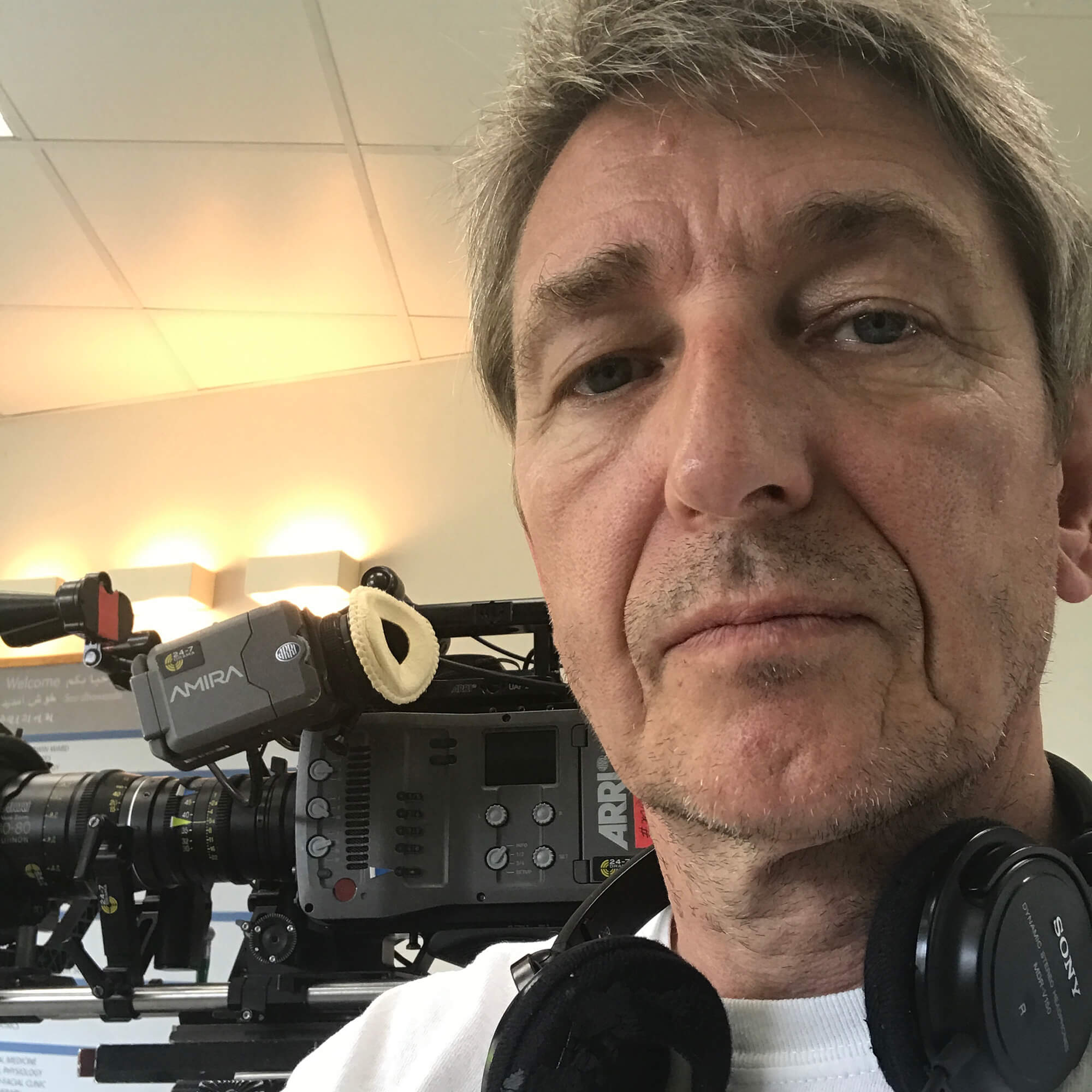 Nigel wearing headphones around his neck standing next to a video camera on a tripod.