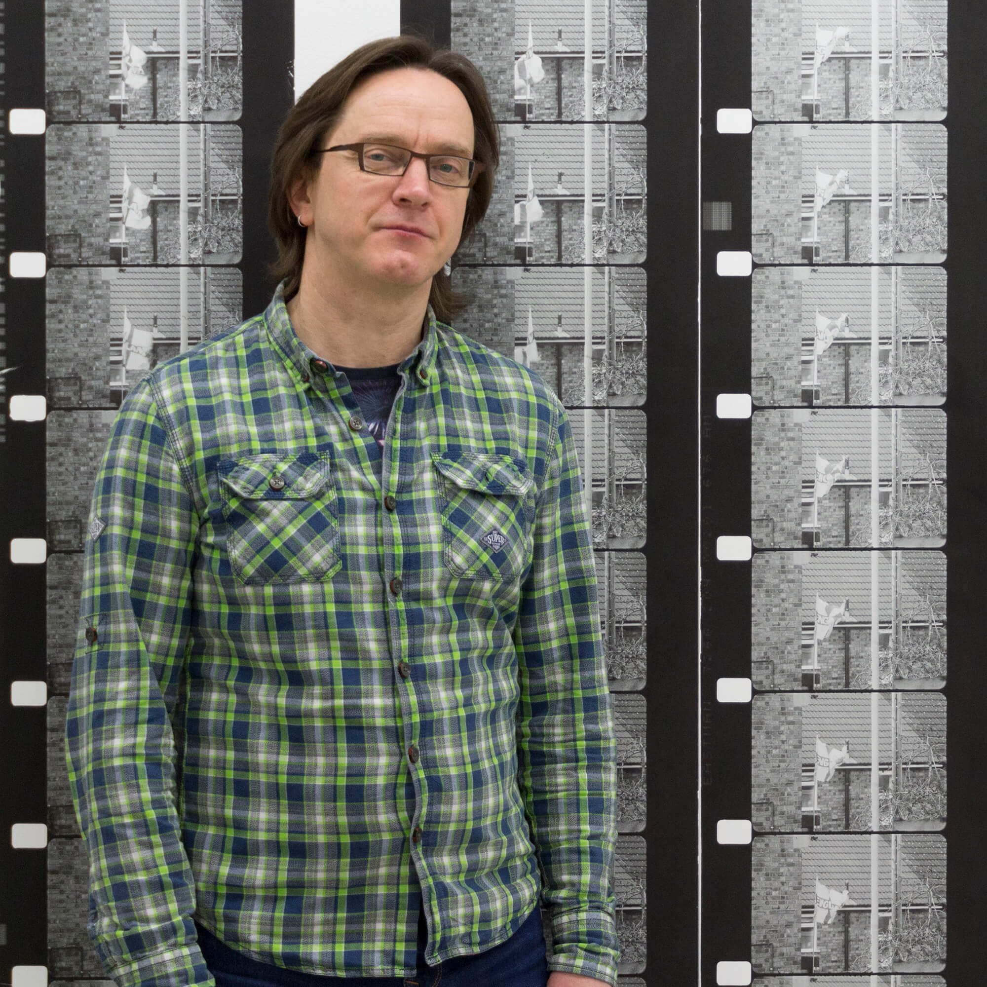 Philip wearing a green, plaid shirt standing in front of film negatives.