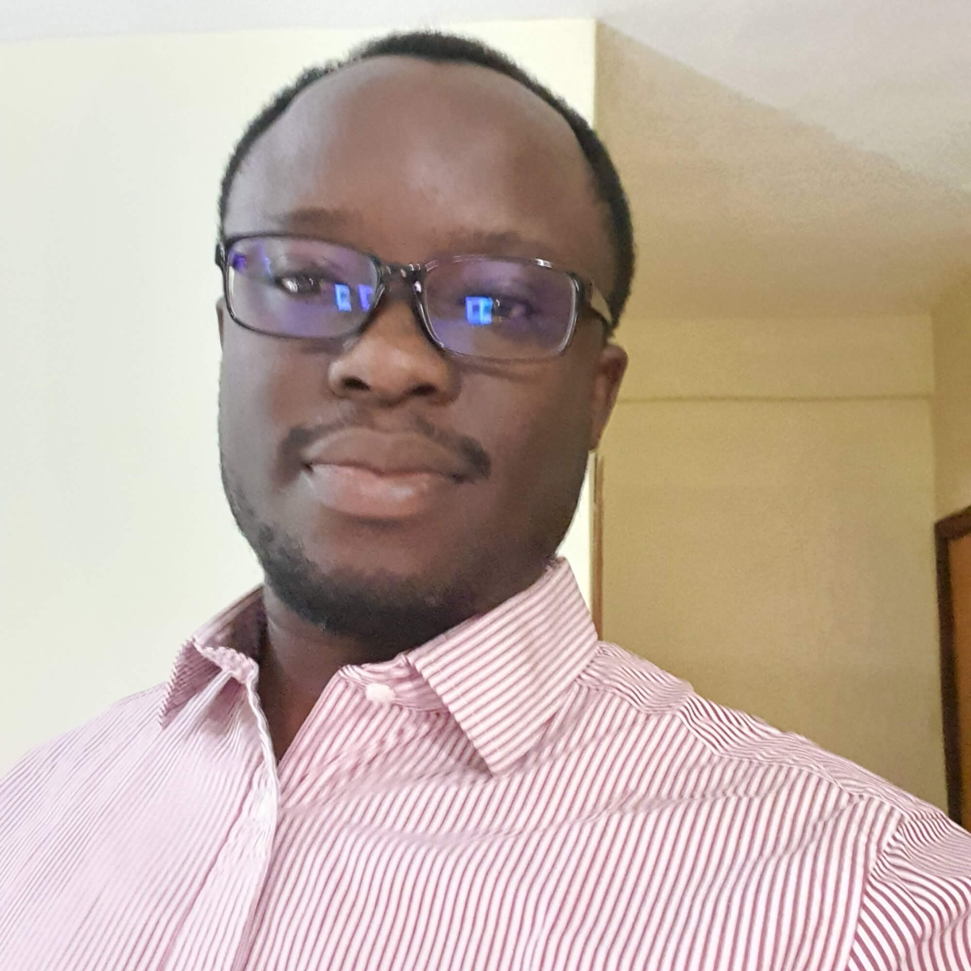 Chinedu wearing a pink striped shirt and glasses.