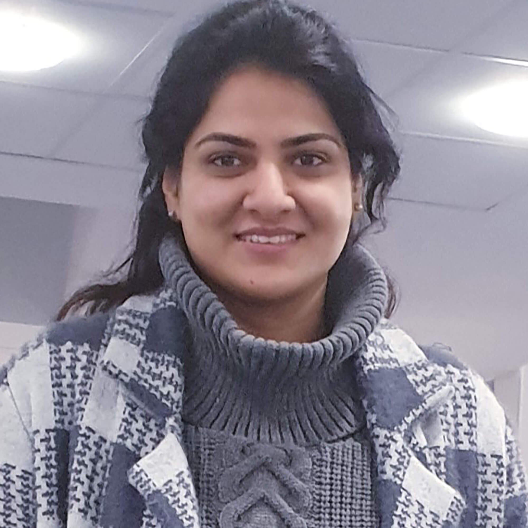 Rabia standing inside a classroom, smiling