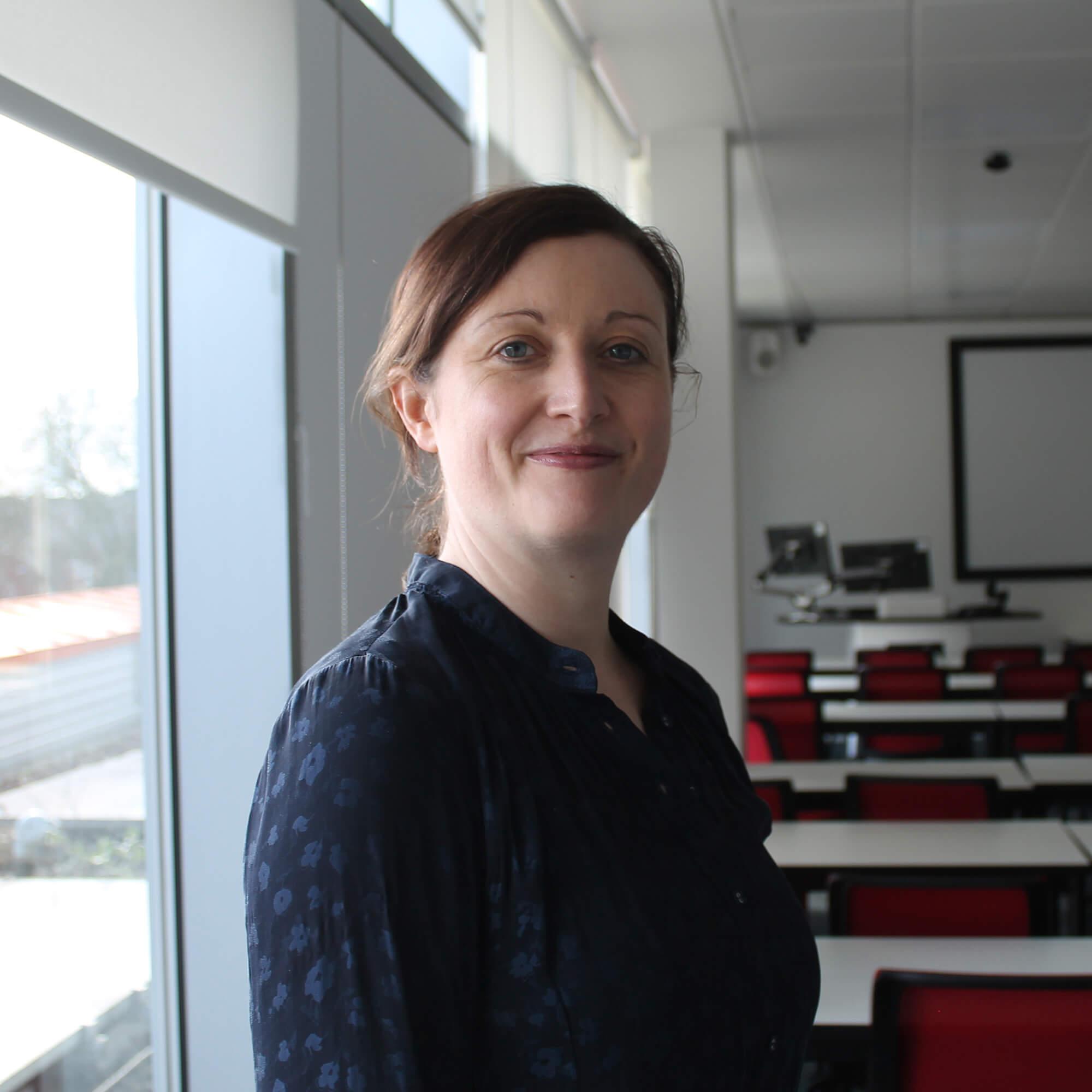 Rachel wearing a blue shirt, standing in a classroom, smiling