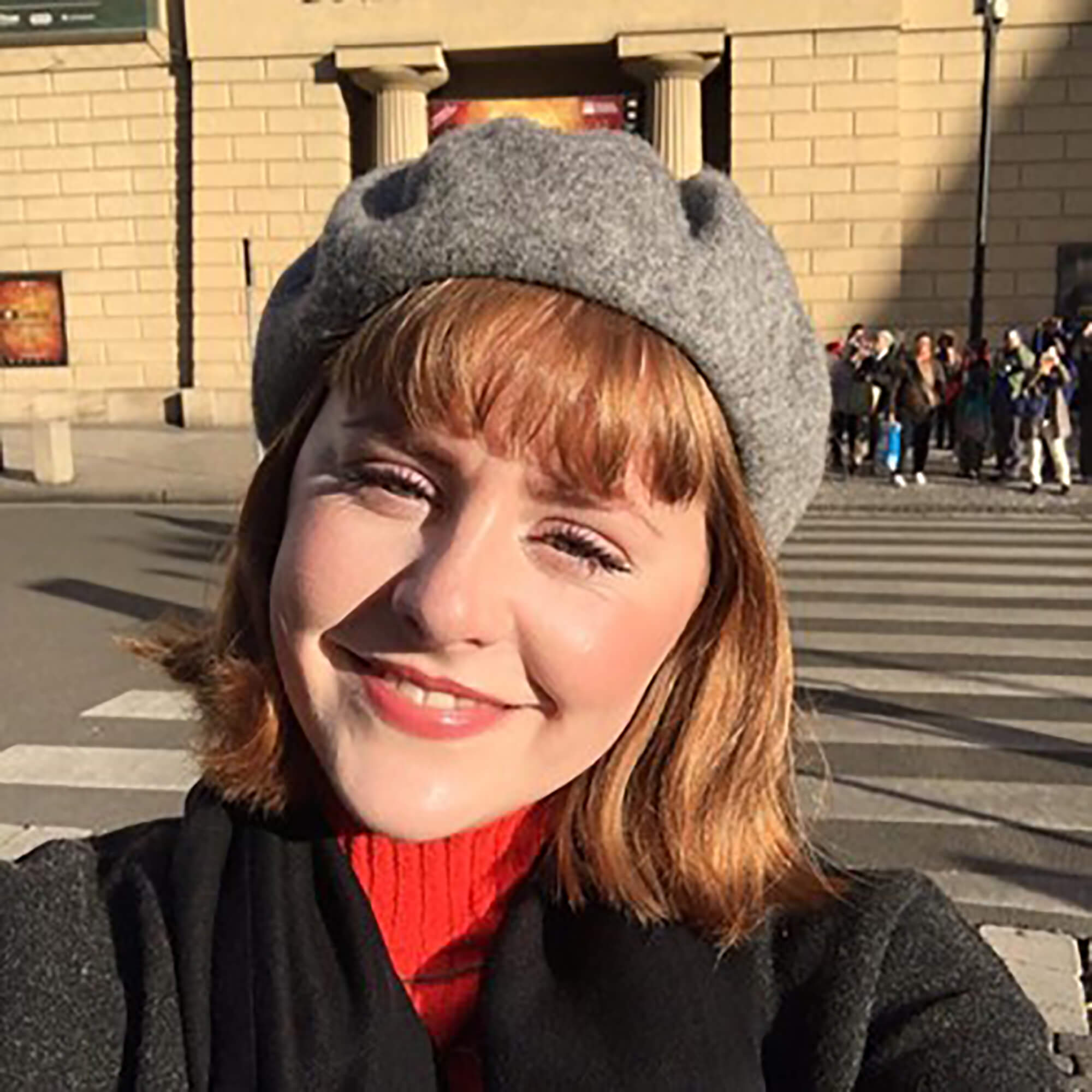 Ruby wearing a grey beret smiling.