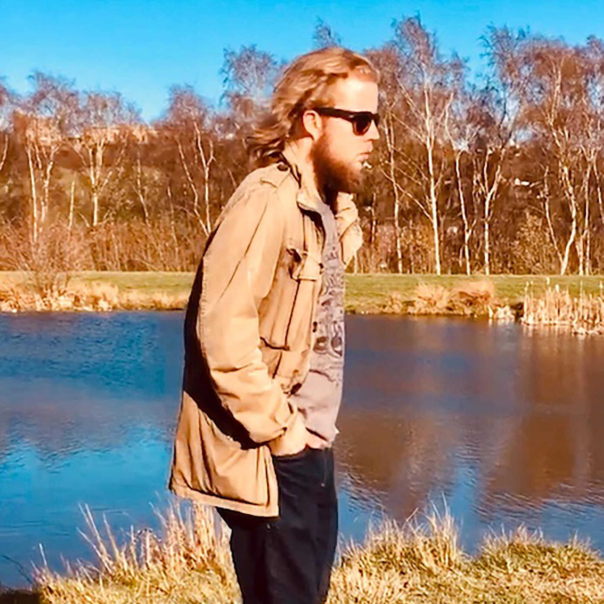 Ryan wearing sunglasses standing by a lake.