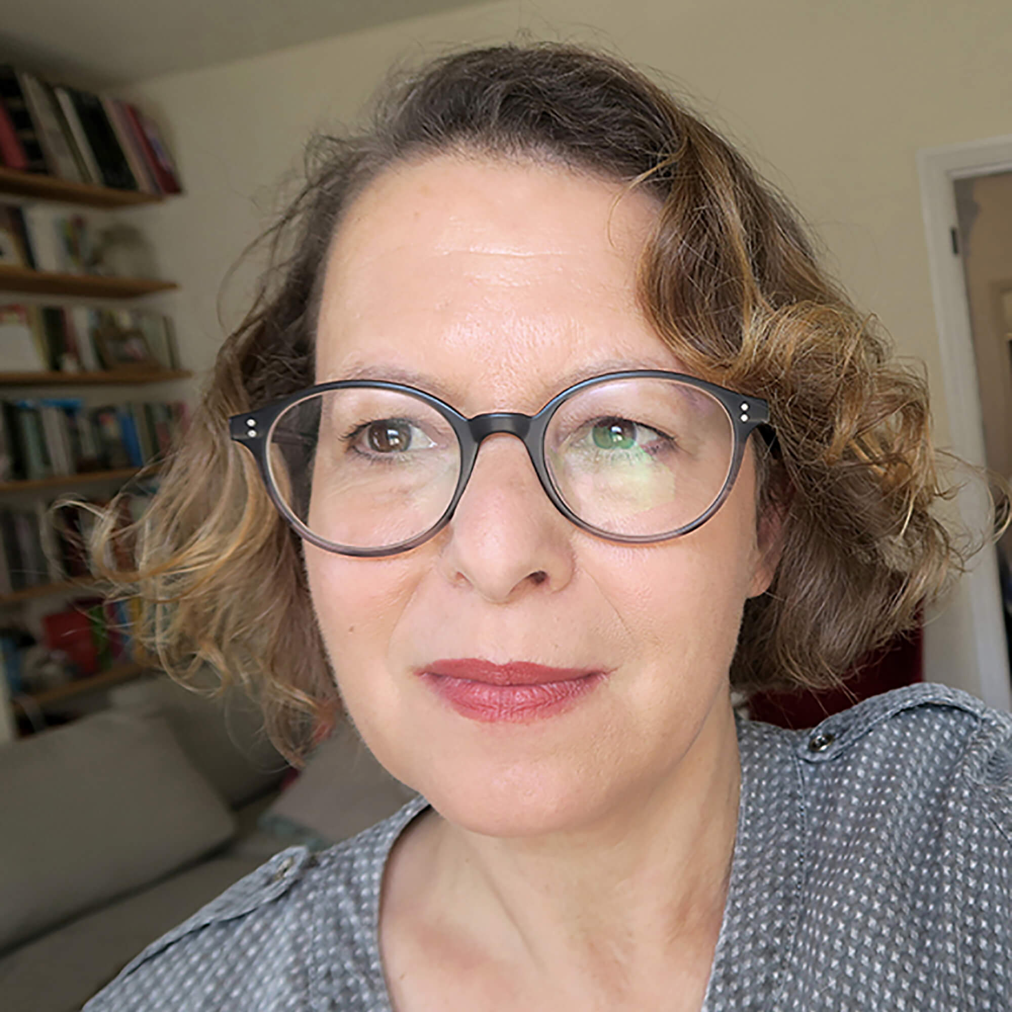 Vered wearing glasses- smiling in front of a bookcase.