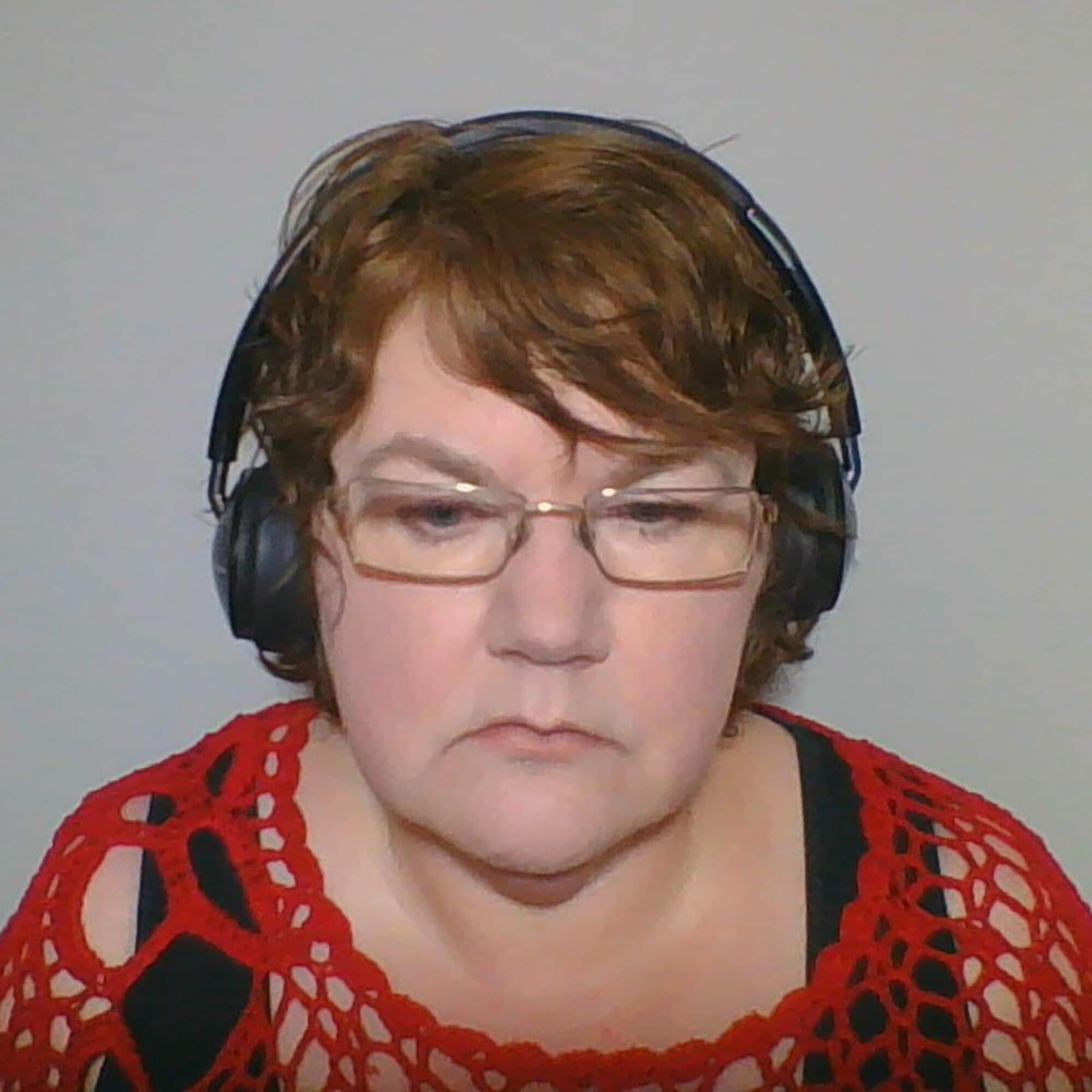 Veronika wearing headphones and glasses, sitting.