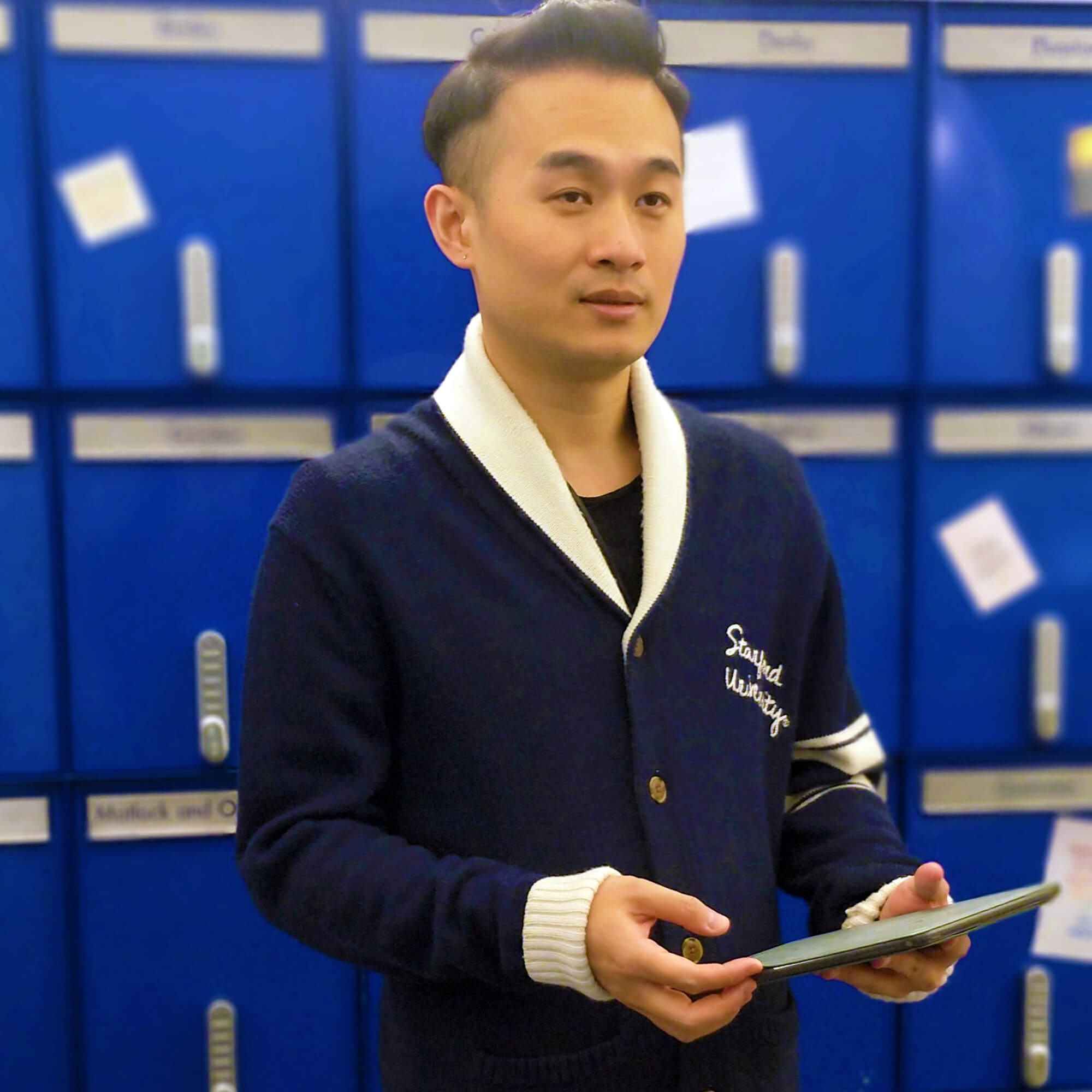 Yutao standing in front of lockers holding a folder