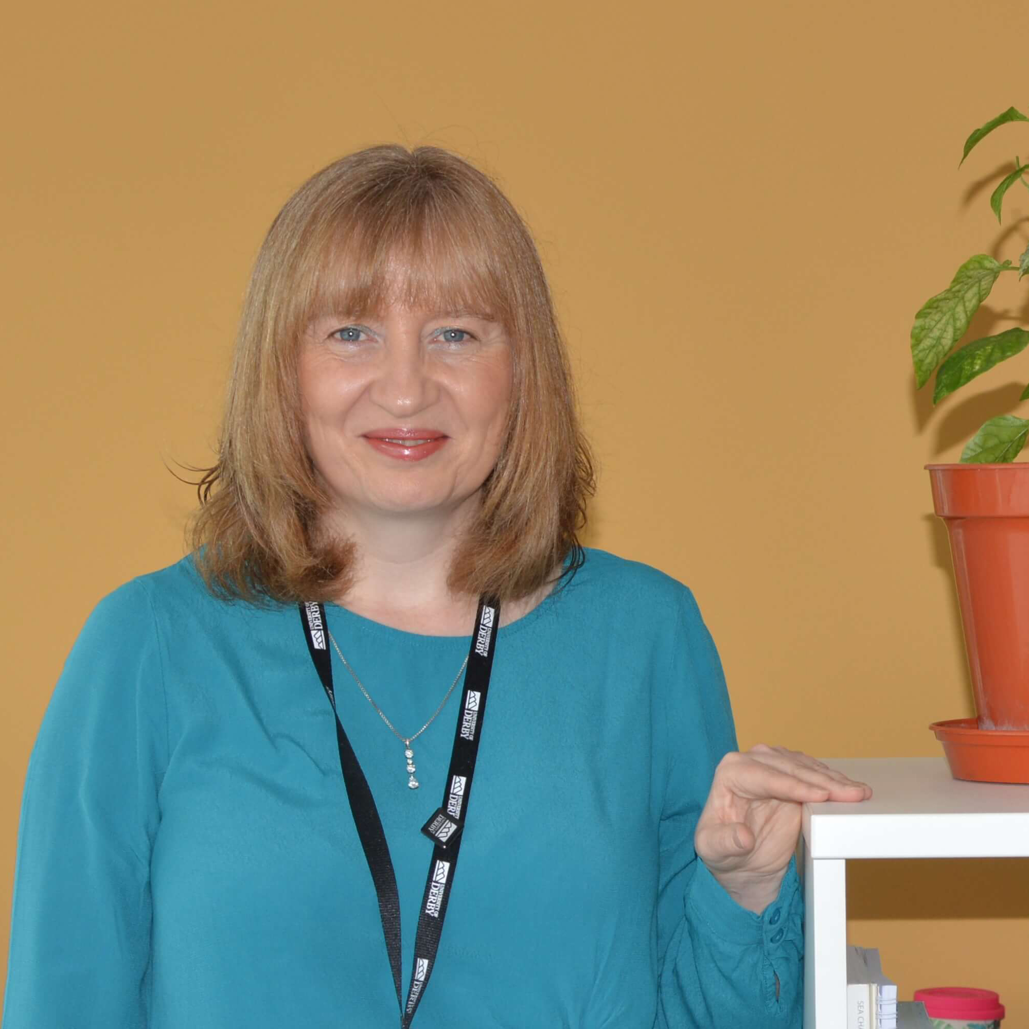 A head shot of Senior Leadership and Strategy Lecturer, Orla Kelleher standing by a bookshelf