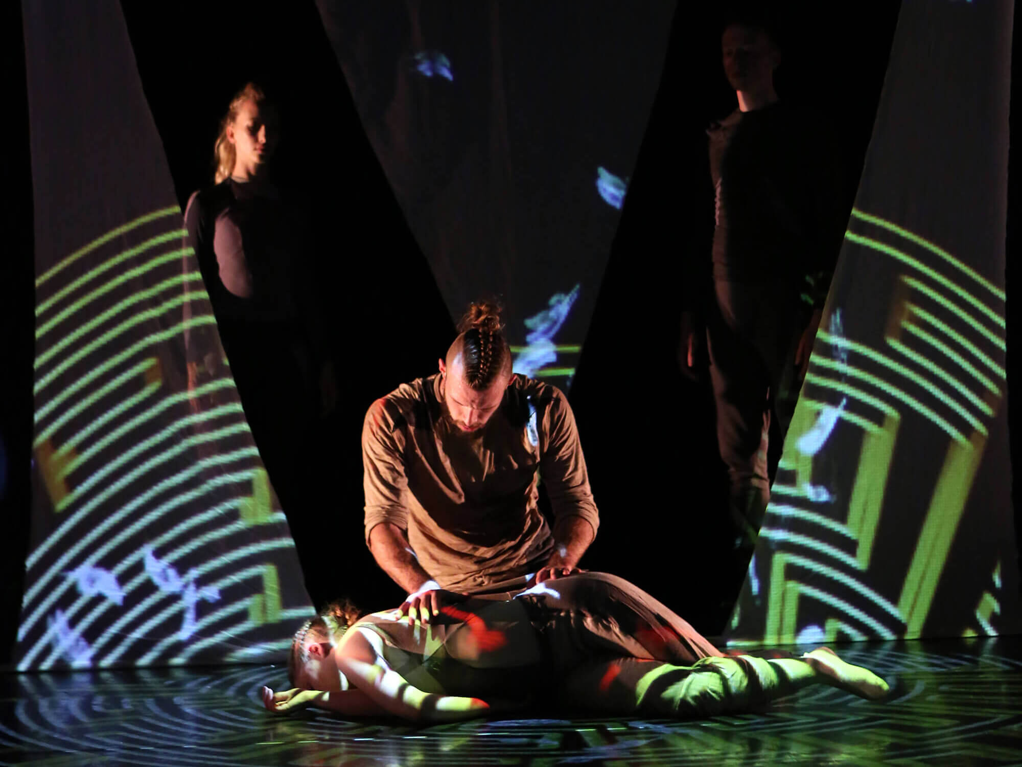 A person lies face down with another person sitting over them. Stage is lit with geometric shapes. Photo: Richard Richards