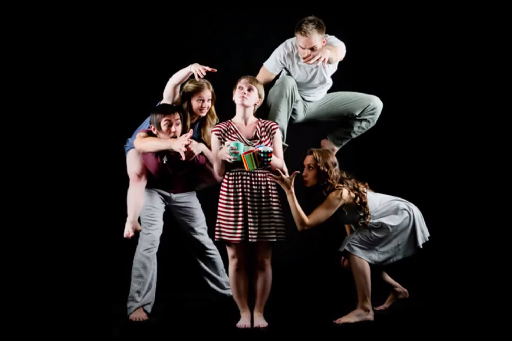 Four people dance expectantly around a woman who is holding five mugs