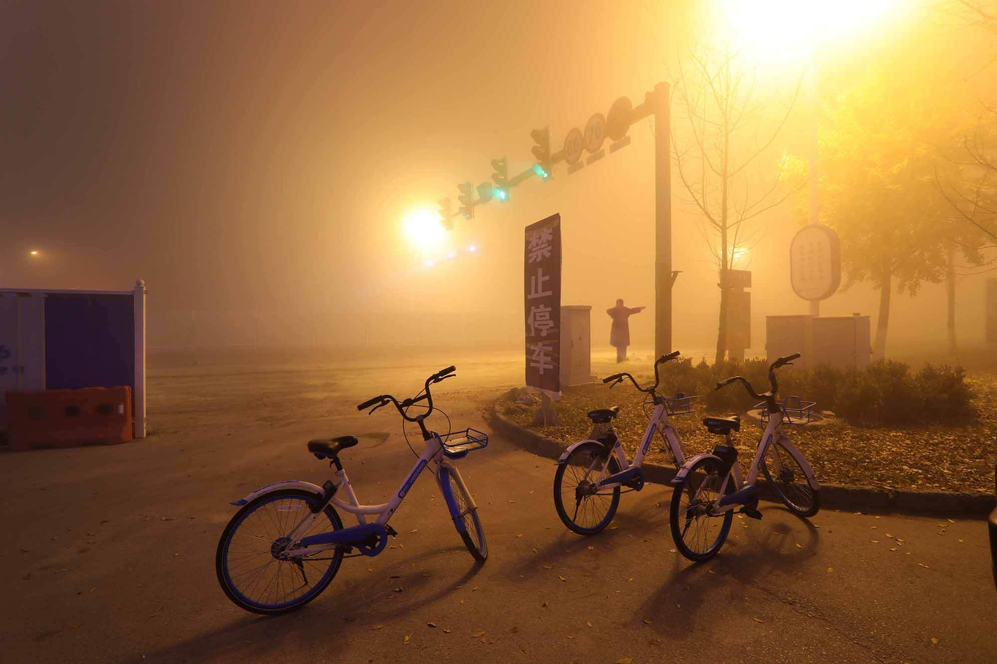 three bicycles on stands beside a set of traffic lights.