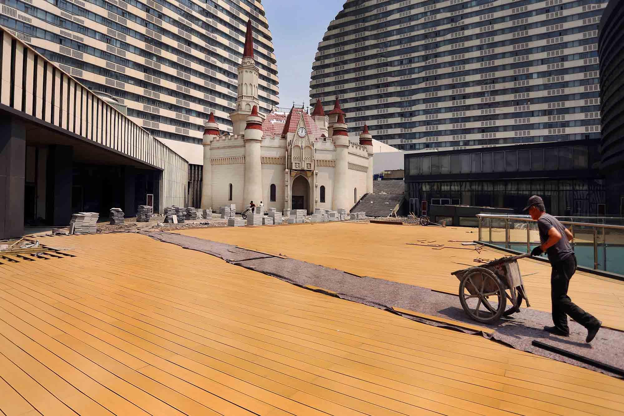 a workman wheels a barrow across a boardwalk area where a fairytale castle is being built between multi-storey buildings
