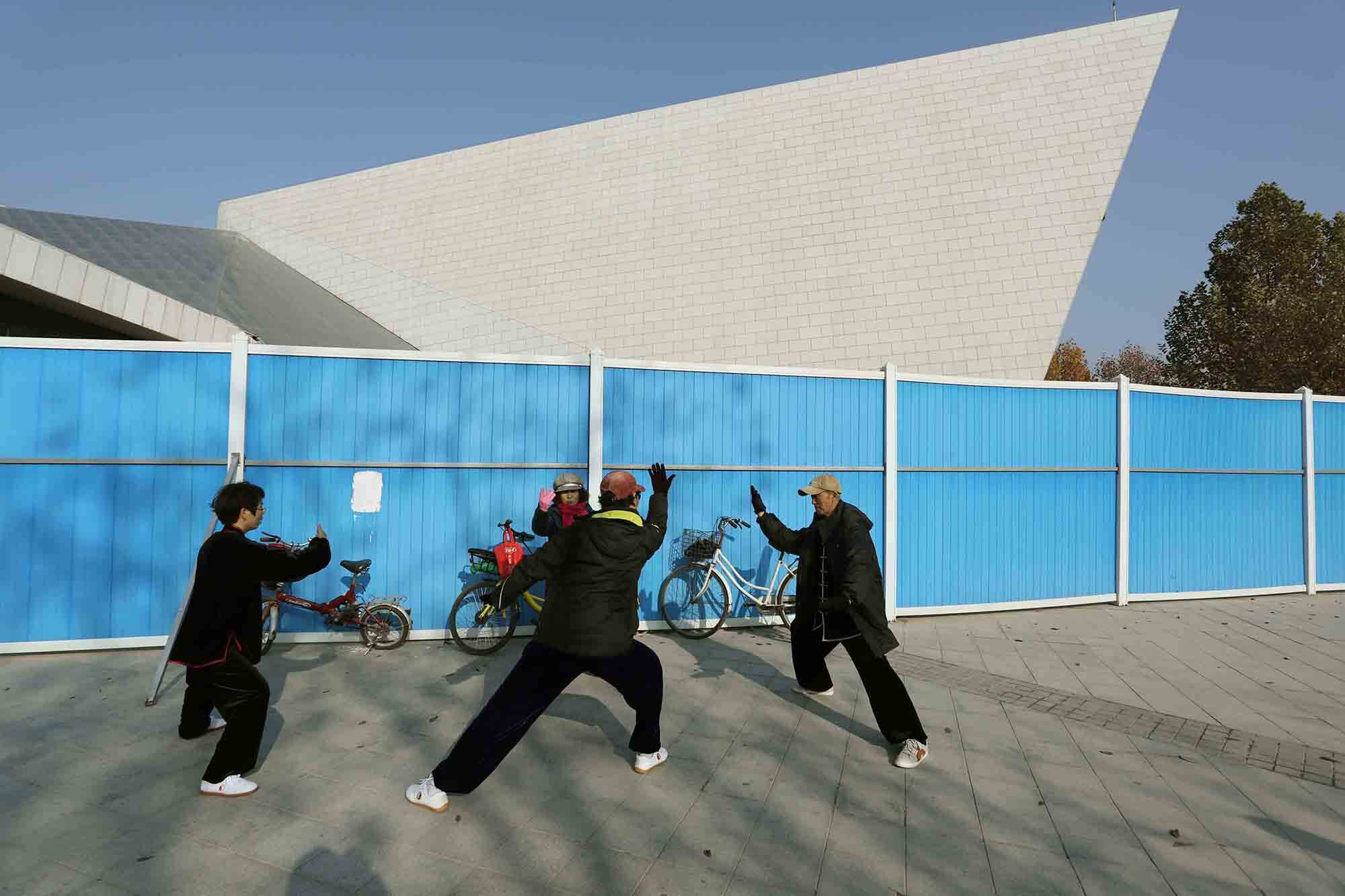 four people practise tai chi next to a fence, beyond which is an angular new building