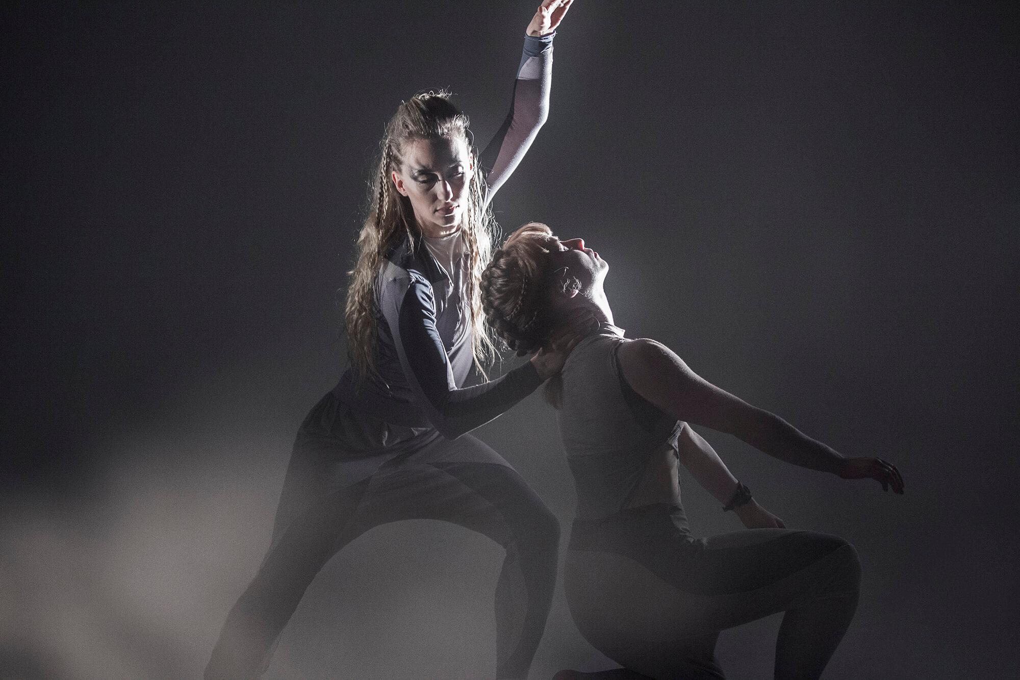 A standing dancer holds a kneeling dancer by the back of the neck. The stage is misty. Photo: Richard Richards