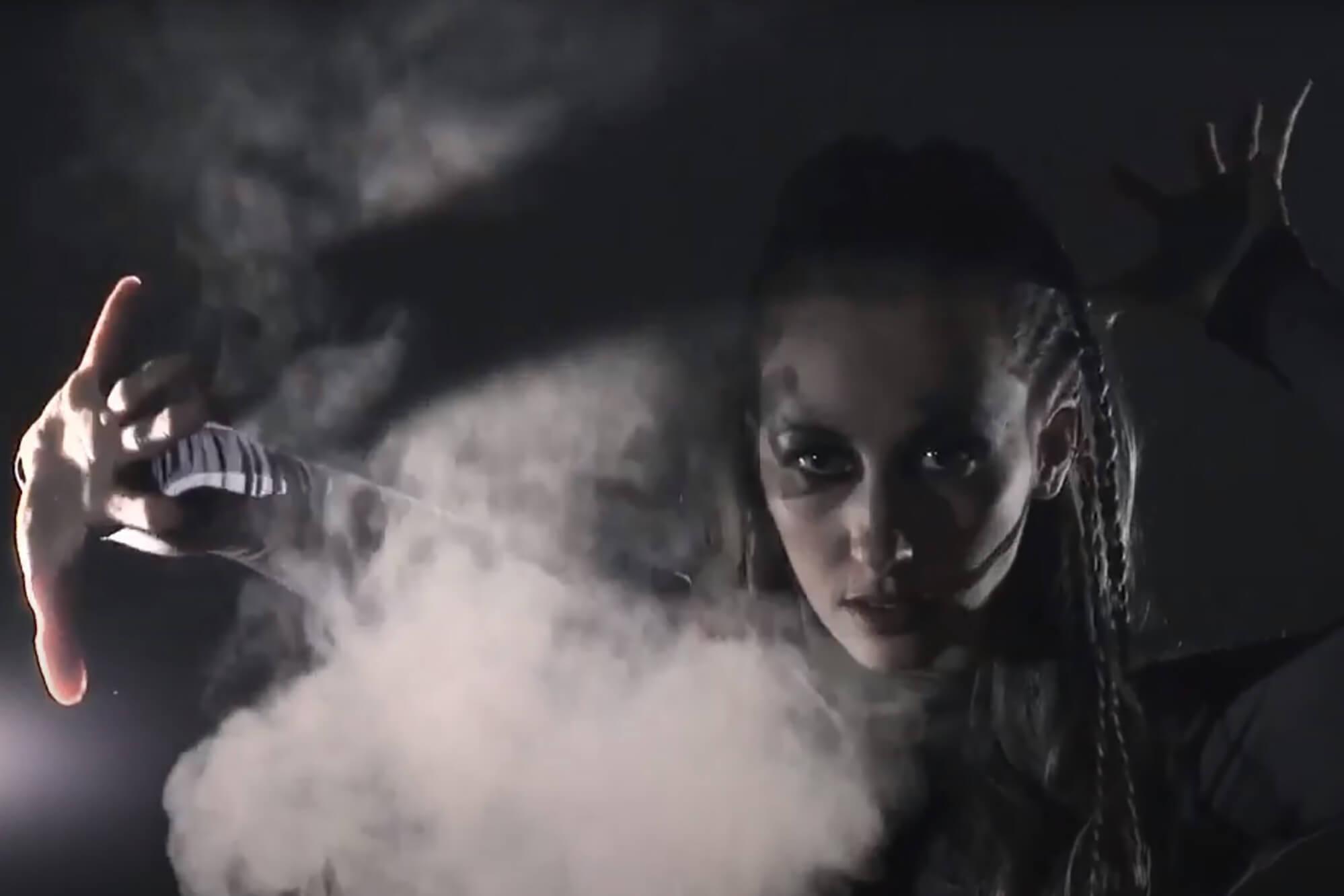 A young woman wearing striking make-up dances through smoke