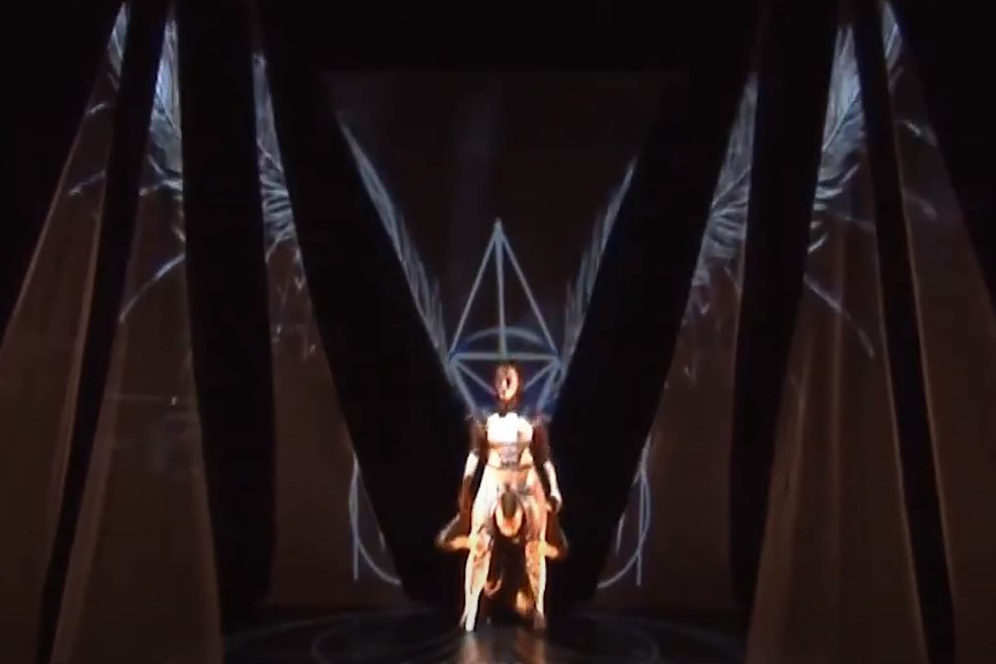 A dancer stands centre stage with wings created by lighting effects.
