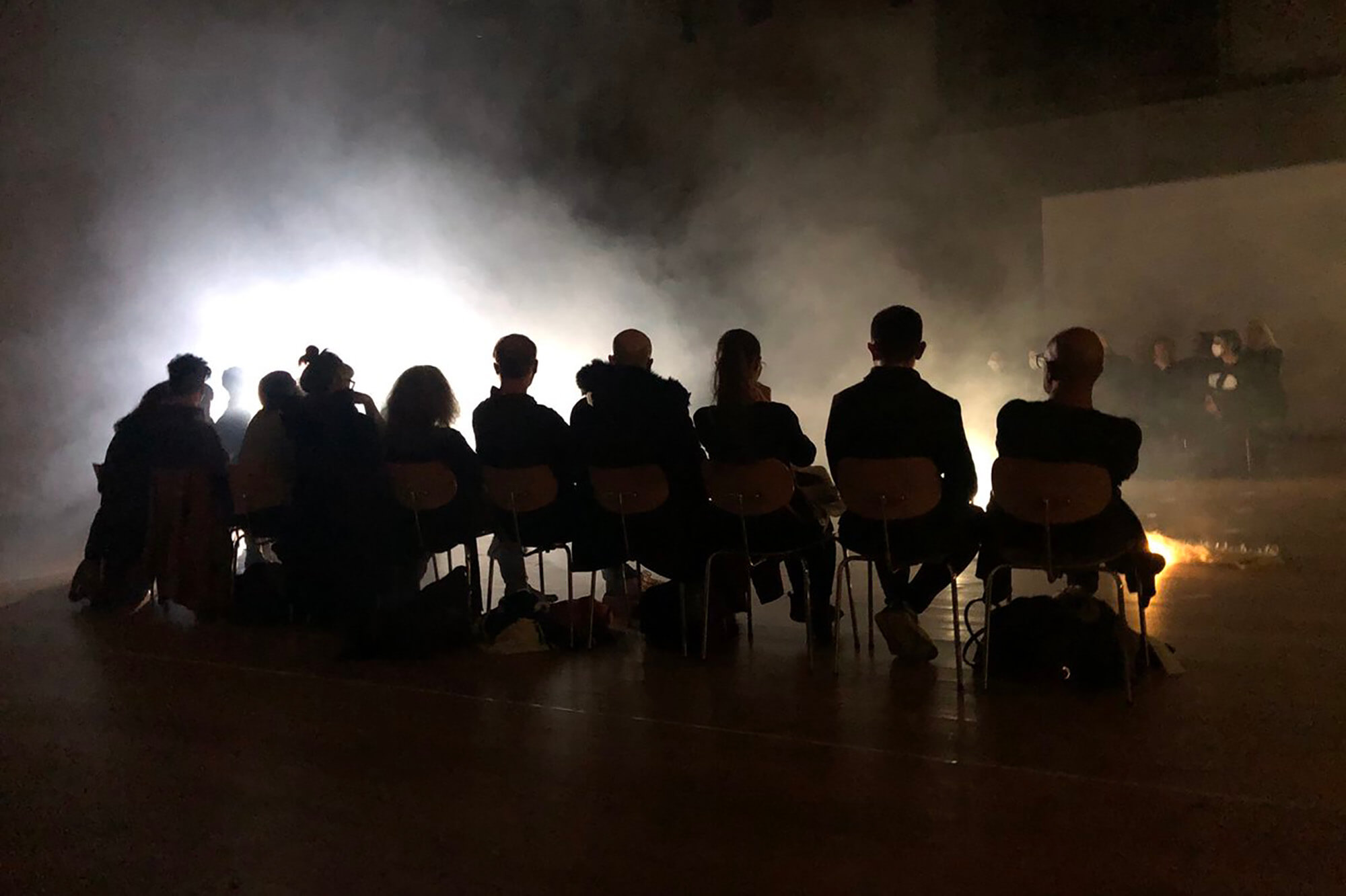 silhouette of the back of a row of audience members sitting on chairs watching a performance involving light and smoke