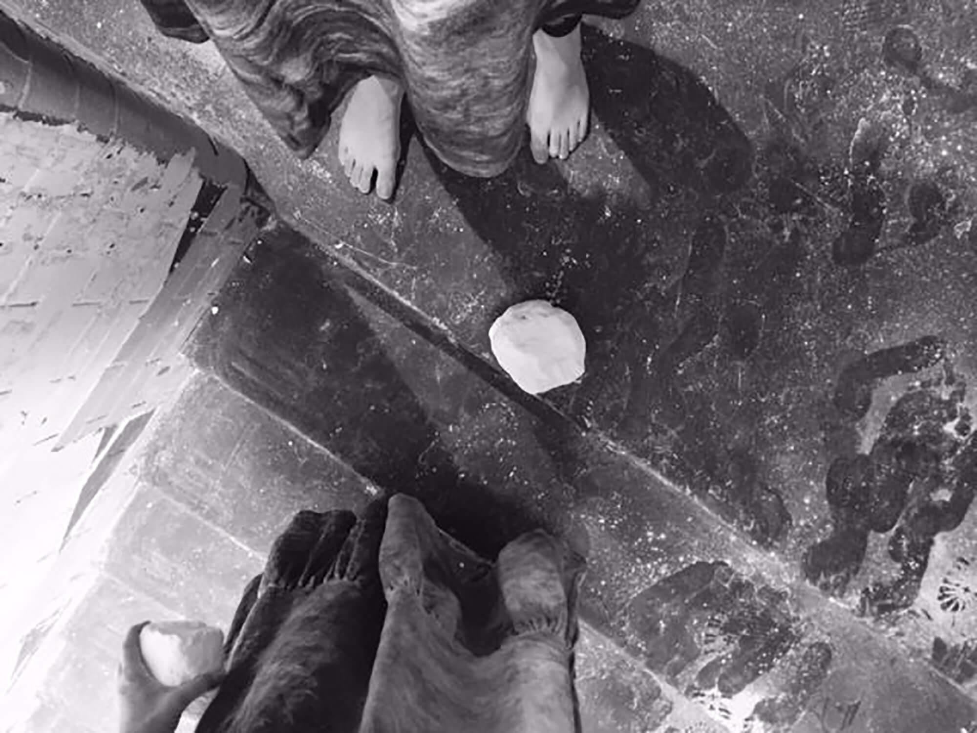Two people stand at the top of a flight of stairs with a lump of chalk on the floor between them