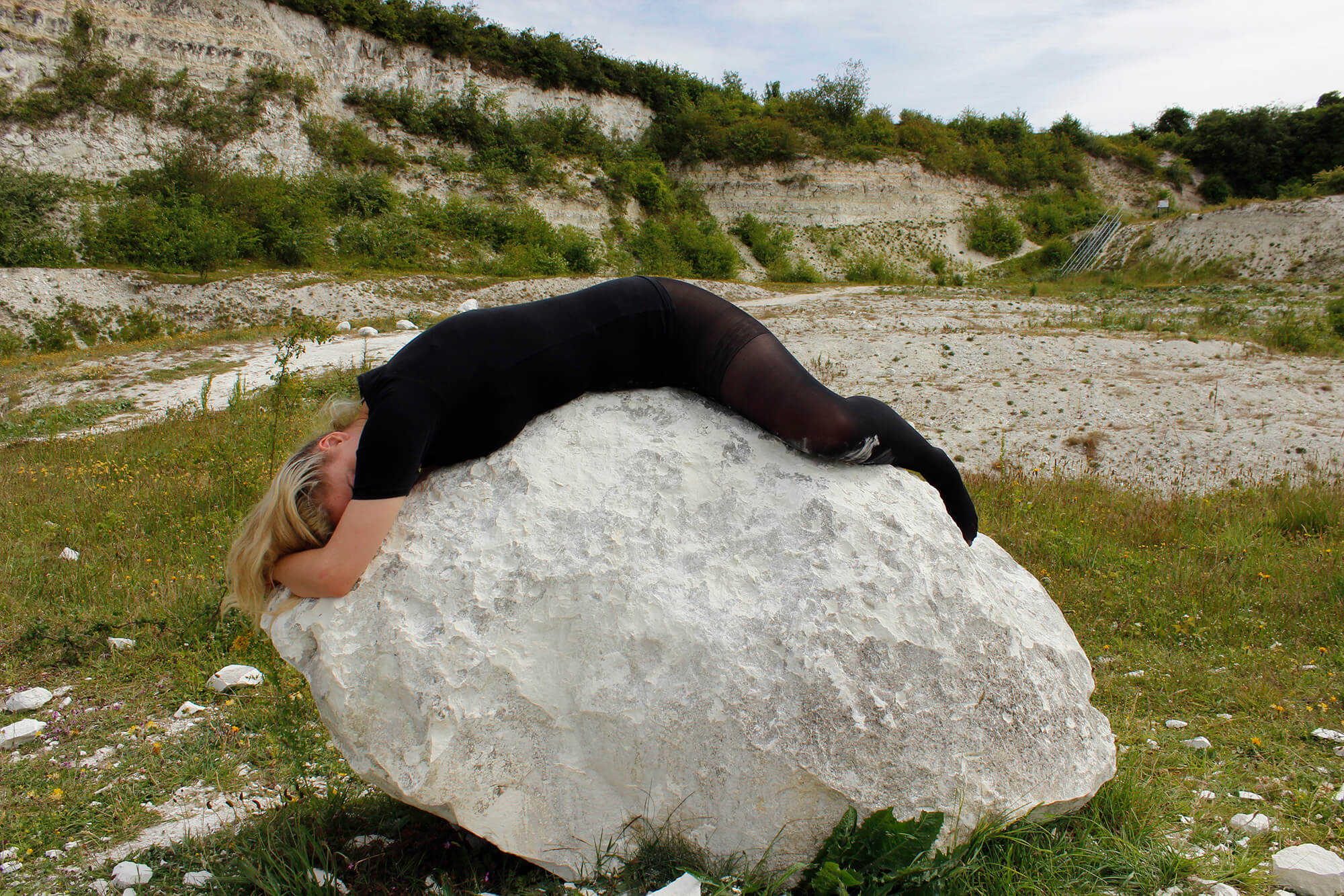 A woman dressed in black lies face down across a chalk boulder in an overgrown quarry