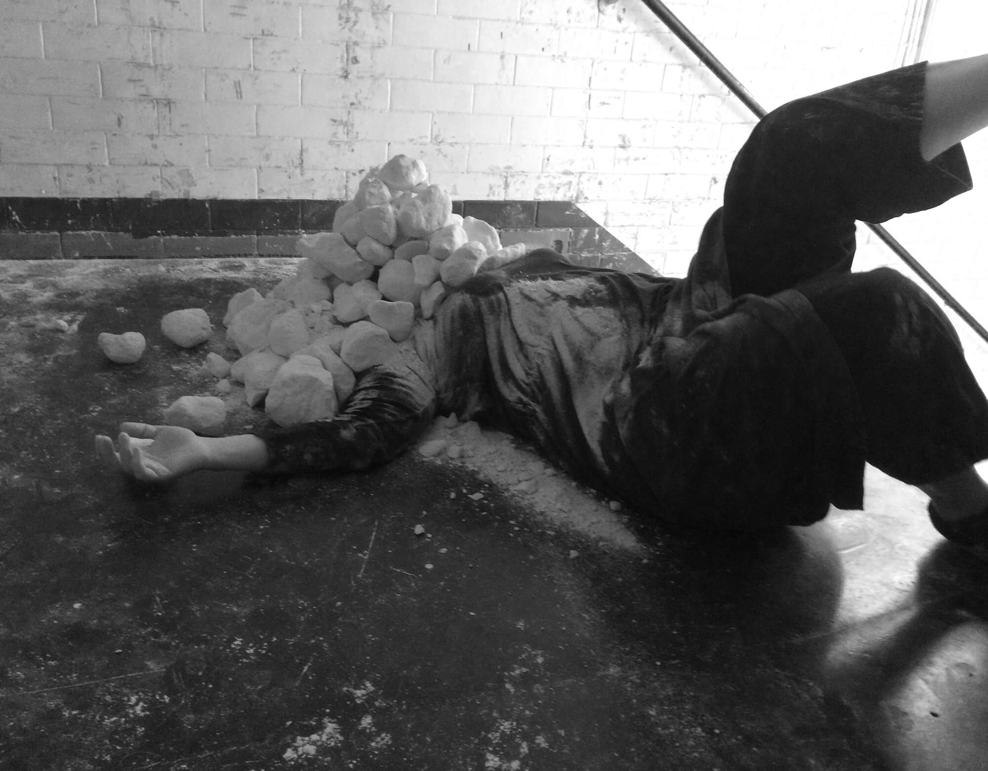 a person lying at the top of a flight of stairs with a pile of small chalk rocks covering their head