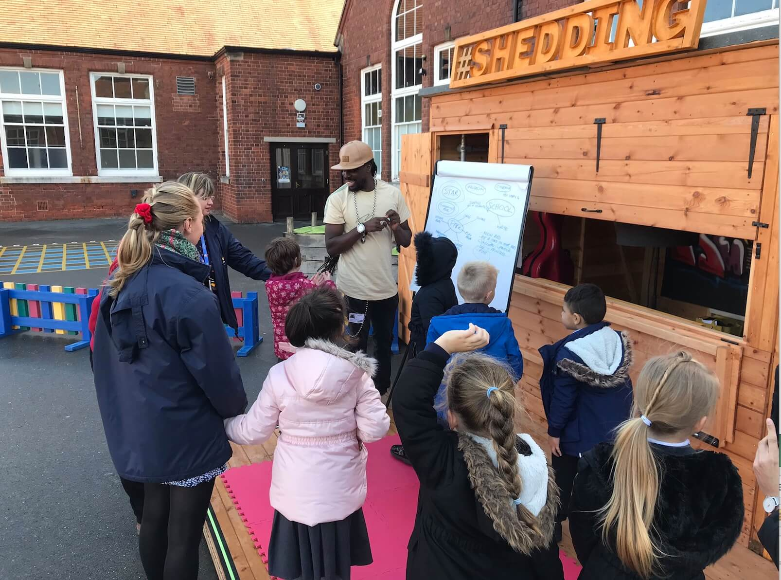Primary school children engage with a facilitator beside S.H.E.D in a school playground