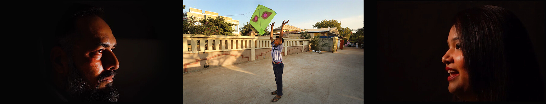 a man and a woman face each other either side of a boy playing outside with a kite