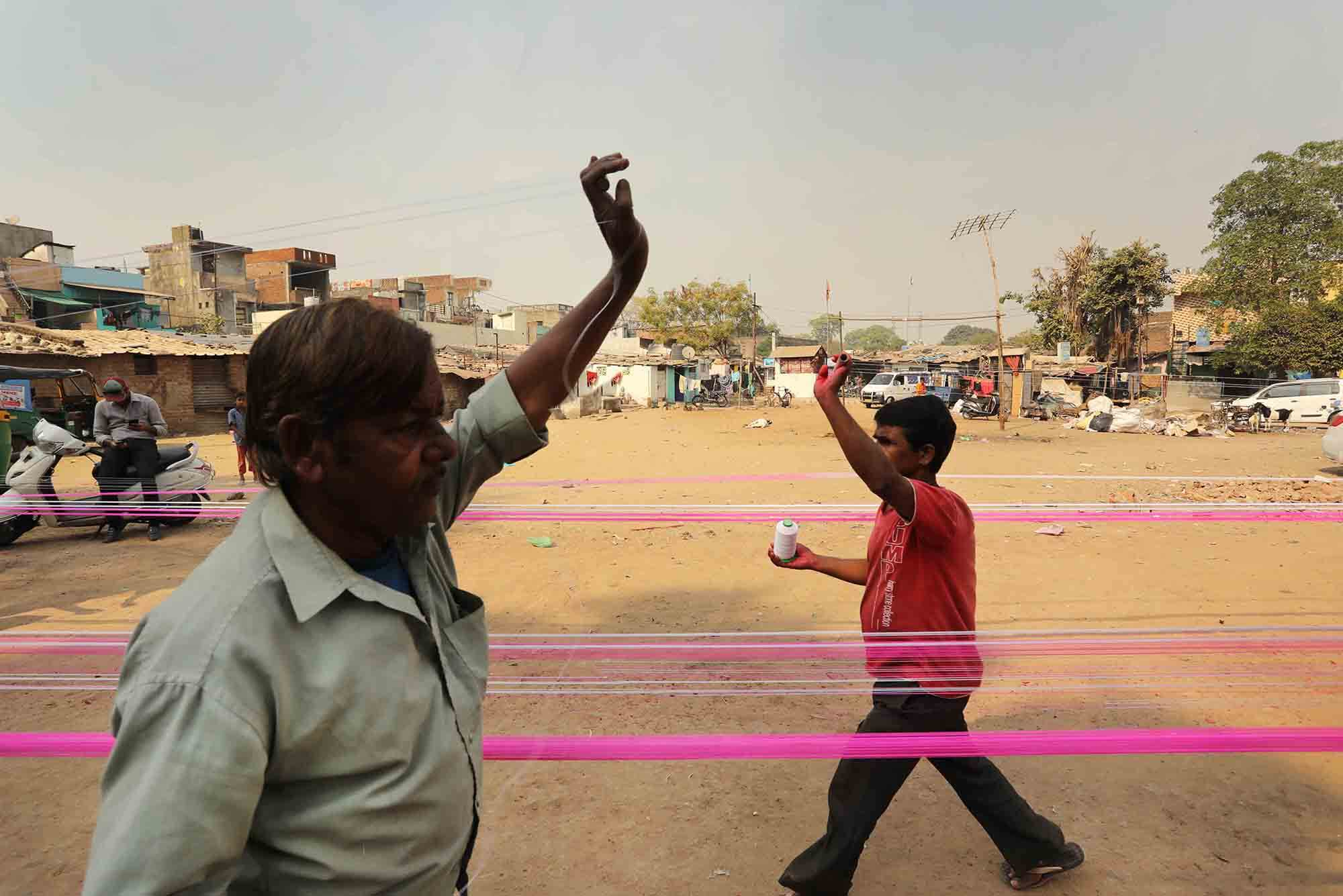two men run lines of coloured thread across an urban space