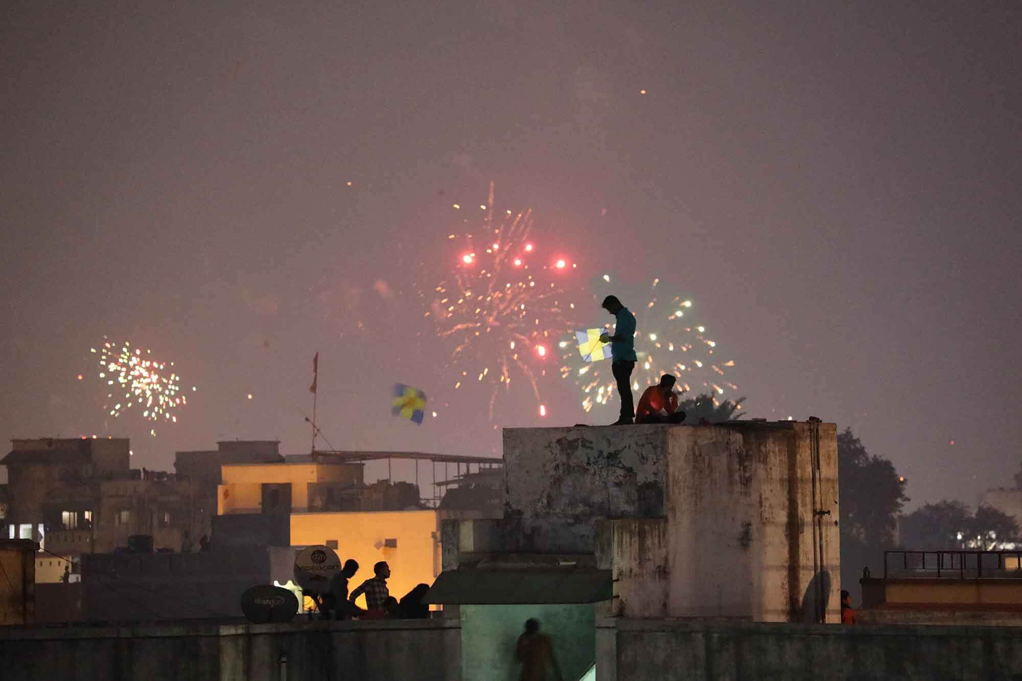 at dusk, men on top of buildings, putting together kites, with fireworks in the distance