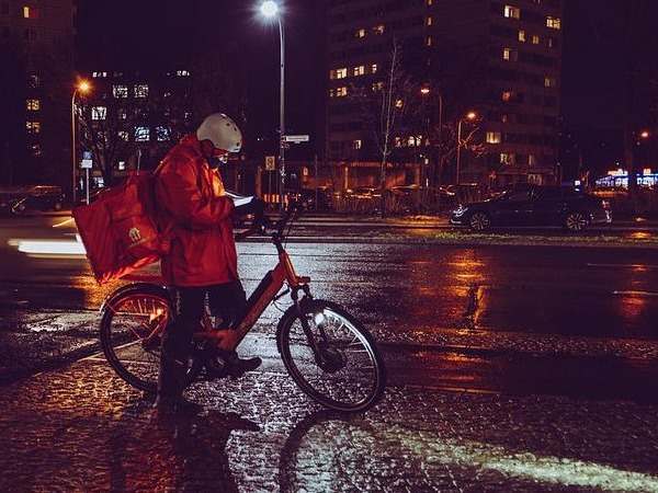 A bicycle courier on a wet street at night sending a text on his mobile phone