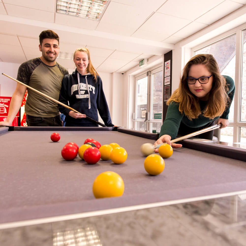 Three students playing pool